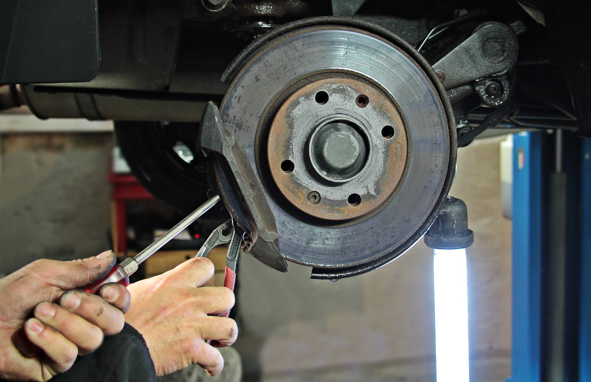 Picture of a auto mechanic working on brake pads